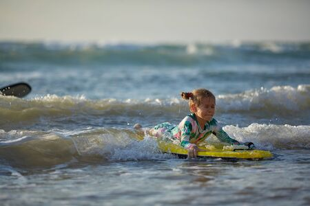 girl with his bodyboard walking into the ocean
