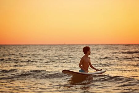 Child surfing on tropical beach. Family summer vacation in Asia. Kids swim in ocean water