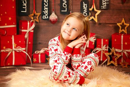Christmas portrait of a happy baby in red Christmas pajamas with a deer on the background of the Christmas presents Stockfoto