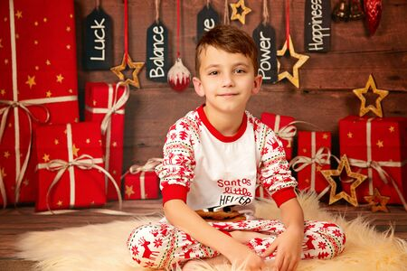 happy cute boy 10 years old on the floor in pajamas waiting for the new year and happy christmas, childhood and family 免版税图像