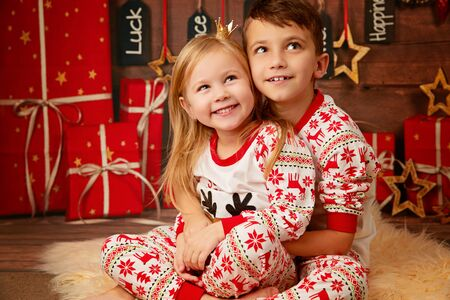 Happy little brother and sister in Christmas pajamas waiting for gifts on Christmas Eve Stockfoto