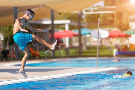 excited teenage boy jumping in the pool