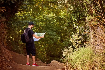 hiker with backpack checks map to find directions in wilderness area