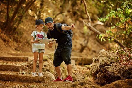 pretty family dad and little cute daughter hiking in a forest, looking at a map and pointing with hand. Stockfoto