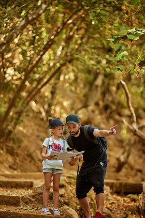 family dad and little cute daughter hiking in a forest