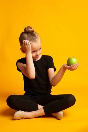 Thoughtful little dancer with apple during break 版權商用圖片