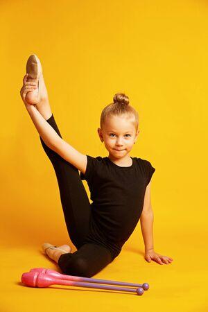 girl gymnast trains with gymnastic clubs on yellow background. childrens professional sports Zdjęcie Seryjne