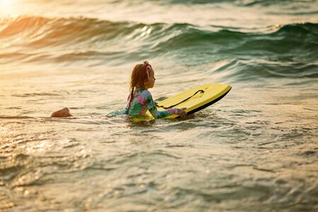 baby girl young surfer ride on surfboard with fun on sea waves. Active family lifestyle
