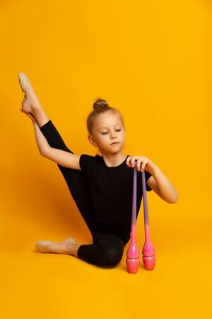 little girl in a black swimsuit stretches her leg and looks down, and holds sports clubs in her hand