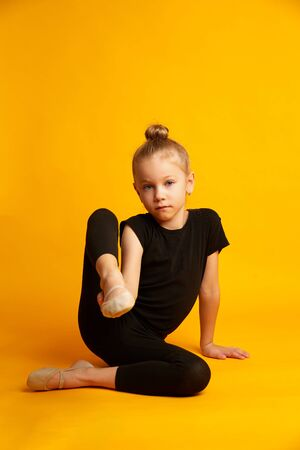 girl in black leotard stretching legs, looking away white sitting against bright yellow background