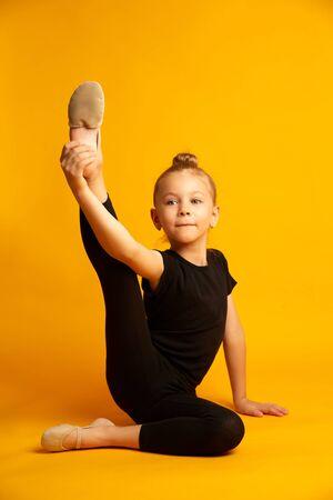 Little dancer in leotard stretching legs during workout
