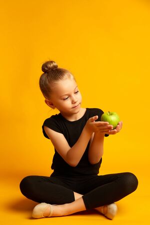 girl in leotard looking at apple while sitting against yellow background during break in training 版權商用圖片