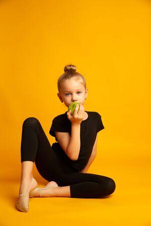 Thoughtful little dancer bites green apple during break