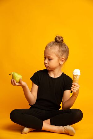Cute little blonde girl choosing between pear and sweet ice-cream on yellow background 版權商用圖片