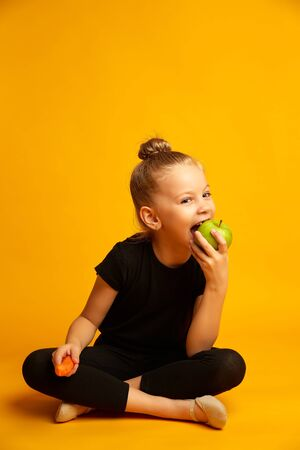joyful little gymnast with a carrot in his hand bites a green apple during a break, studio shot on a yellow background 版權商用圖片