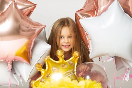 Little girl playing with balloons. Portrait of little girl playing with air balloons. Happy little girl holding colorful balloons.Smiling kid. Banco de Imagens - 138190472
