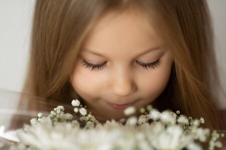 close-up of the blonde girl with closed eyes enjoying a white bouquet of wild flowers
