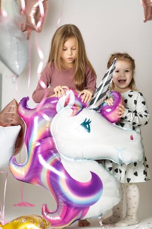 Two little girls play with a big unicorn balloon surrounded by balloons
