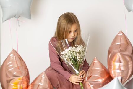 Cute Blue-eyed blond girl in a dress holds a bouquet of white flowers on a white background with multi-colored balloons