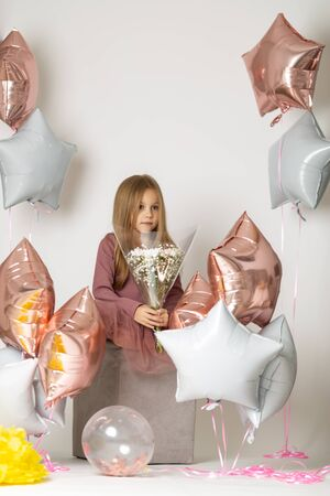 seven year old girl sitting on a white background dress with a bouquet of white wildflowers and balloons