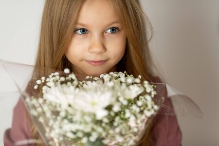 beauty young blond girl with a bouquet of wildflowers with weathered lips