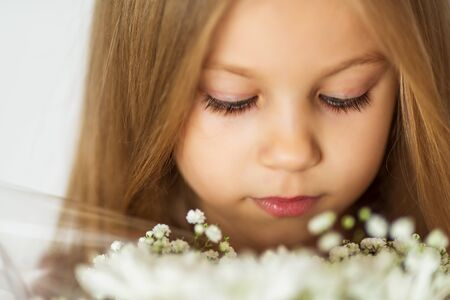 close up beautiful little blond girl with a bouquet of wildflowers with weathered lips