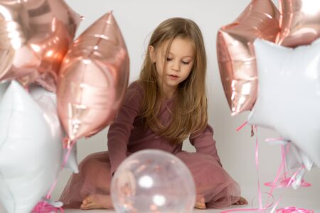 Sweet little girl with air balloons in studio