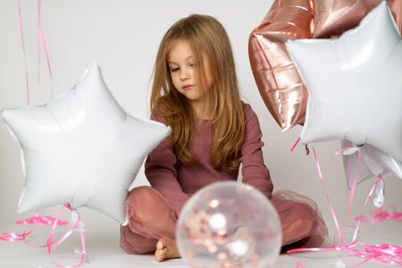 Portrait of sad Caucasian blond little girl with colorful balloons over white background