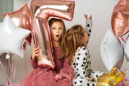 portrait of two sisters, 7-year-old blonde and 3-year-old child, sisters play with balloons, ball number seven Stock fotó