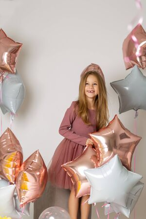 Happy beautiful little girl holding a silver gel balloon in the form of stars. Birthday celebration