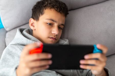boy plays video games on a portable console