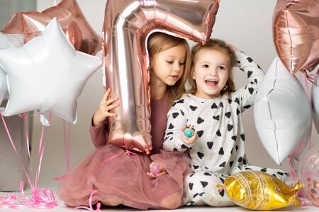 Happy Birthday 7 year. little girls in evening dress looking out of a balloon in the shape of a seven on white background with beads Stock fotó