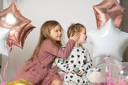 Whispering A Secret. Preschool girl telling her friend some gossips
