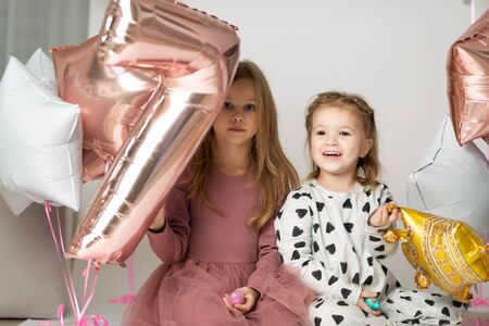 funny girls play with a balloon as a number seven