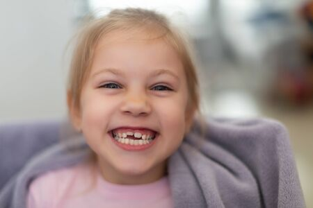 Cheerful smiling cute child with teeth dropped out preschooler girl with open mouth without milk tooth Stock Photo