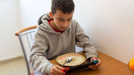 Kid eating rice and surfing on internet or playing video games on console 写真素材