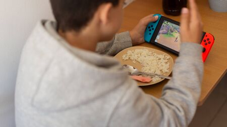 Kid eating rice and surfing on internet or playing video games on console. boy eats poorly distracted by the game.