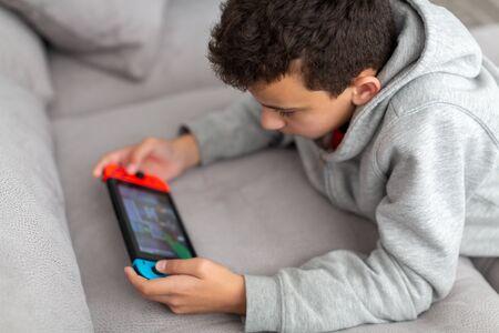Adolescente se acuesta en un sofá y juega un juego. Tiene una consola de juegos portátil en sus manos. Cómo los adolescentes pasan sus vacaciones. Foto de archivo