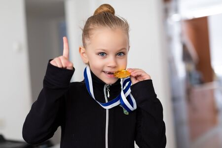 Portrait of a little girl-gymnast in a tracksuit with medals on the neck, biting the medal and showing thumbs up Stock fotó