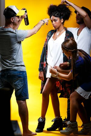 tel Aviv December 12, 2019: a group of stylists working on the image of a young model on a yellow background