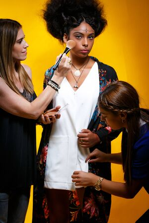 Tel Aviv December 12 2019 Stylist and a model. Fair haired positive stylist doing makeup to an African American model