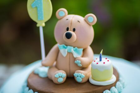 close up Amazing cake for boys first Birthday. Blue and white colors with Bear cub from sugar mastic