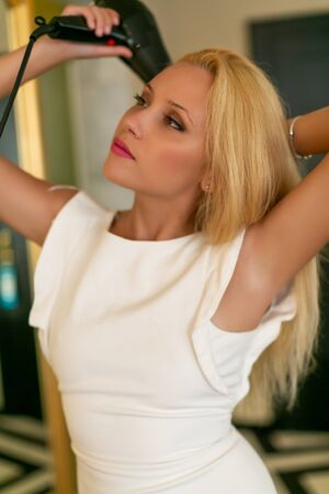 Hair Dryer. Beautiful Woman Drying Healthy Long Straight Hair Using Hairdryer