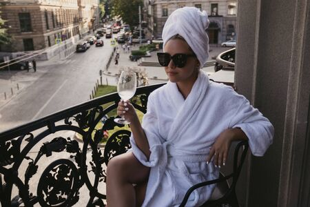Young beautiful girl in a dressing gown sits on a balcony with a glass with wine Reklamní fotografie
