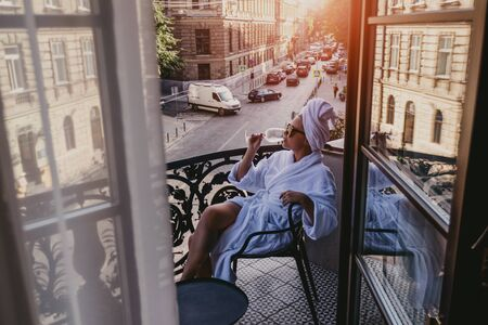 View from the hotel window on a girl relaxing in a bathrobe with a white glass of wine