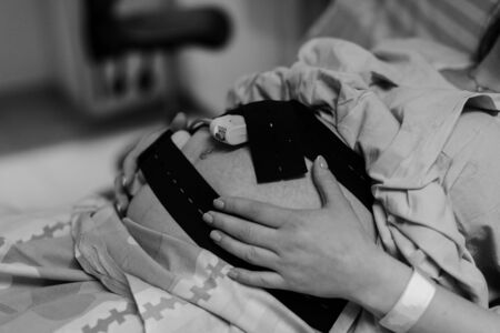 Pregnant woman in hospital with cardiotocography bell black and white photo