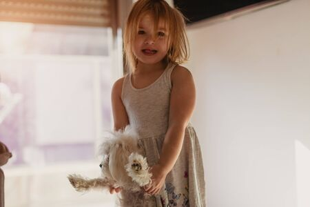 Adorable little girl with her dog at home