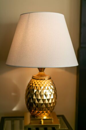 Luxurious golden lamp on the night table next to the bed Reklamní fotografie