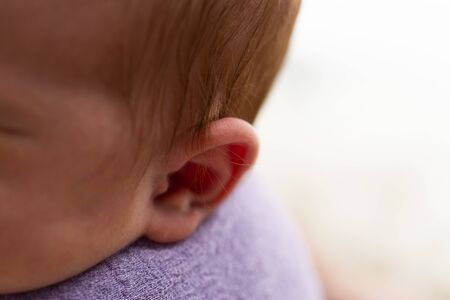 Babys ear in close up on a mat