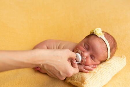 babyhood, motherhood and people concept - mothers hand giving pacifier to little baby daughter lying on knitted yellow blanket of knitted pillow Reklamní fotografie
